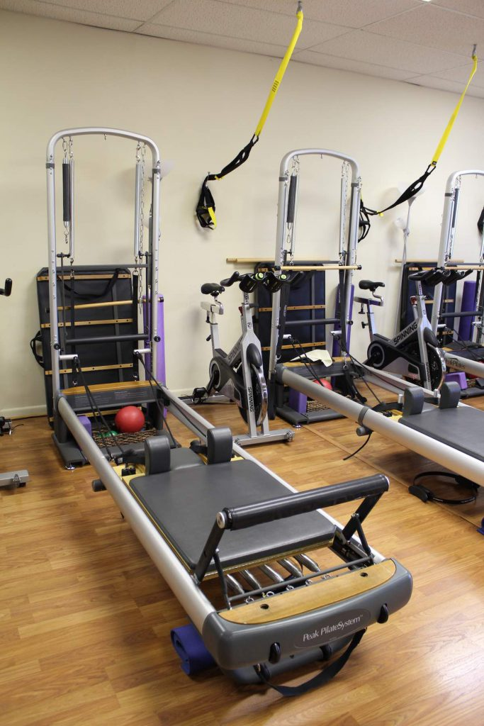 iBeyond Pilates Studio showing Reformer Machine, TRX suspension equipment, and spin bikes.